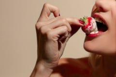 Frau, die eine Erdbeere bedeckt in der Creme isst Lizenzfreie Stockfotografie