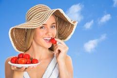Frau, die eine Erdbeere isst lizenzfreies stockfoto