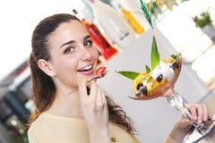 Frau, die eine Erdbeere und ein Eisdessert in einer Stange isst Stockfotografie