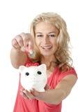 Frau, die eine Euromünze in Sparschwein einsetzt Lizenzfreies Stockfoto