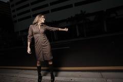 Frau, die eine Fahrt in der Dunkelheit hitching ist Stockfoto