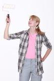 Frau, die eine Farbenrolle verwendet Stockfotos