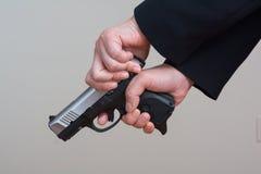 Frau, die eine Faustfeuerwaffe spannt stockfotos