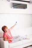 Frau, die eine Fernsteuerungsklimaanlage hält Stockfotografie