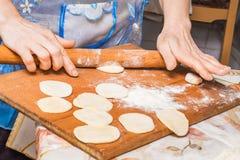 Frau, die eine festliche Mahlzeit von einem Teig, kochend am home_ vorbereitet lizenzfreies stockfoto