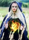 Frau, die eine Feuerkugel hält lizenzfreie stockfotos