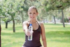 Frau, die eine Flasche kaltes Wasser im grünen Park anhält stockfoto