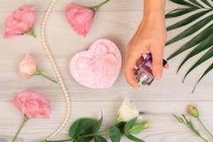 Frau, die eine Flasche Parfüm in der Hand mit Blumen auf dem Hintergrund hält lizenzfreies stockfoto