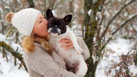 Frau, die eine französische Bulldogge im Schnee küsst stockbild