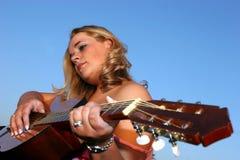 Frau, die eine Gitarre spielt lizenzfreie stockfotografie