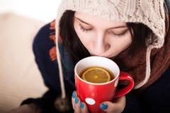 Frau, die eine große Schale frisch gebrauten heißen Tee genießt, wie sie auf einem Sofa im Wohnzimmer sich entspannt Lizenzfreies Stockbild