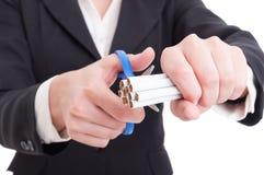Frau, die eine Hand von Zigaretten unter Verwendung der Scheren oder der Scheren schneidet Lizenzfreie Stockbilder
