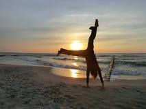 Frau, die eine Handstandveränderung während des Sonnenuntergangs tut Lizenzfreies Stockbild