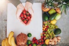 Frau, die eine Handvoll frische Erdbeeren über dem Hacken des Ebers hält Lizenzfreies Stockfoto