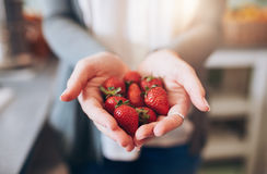 Frau, die eine Handvoll frische Erdbeeren hält lizenzfreie stockbilder