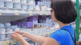 Frau, die eine Kaffeetasse im Speicher wählt stock footage
