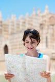Frau, die eine Karte während am Feiertag liest stockfotografie