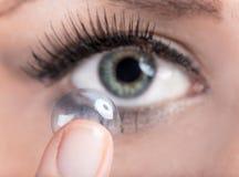 Frau, die eine Kontaktlinse einsteckt Lizenzfreie Stockfotografie
