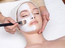 Frau, die eine kosmetische im Gesichtschablone hat Stockbilder