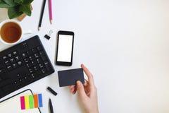 Frau, die eine Kreditkarte auf weißem Schreibtisch mit Smartphone und Tastatur hält stockbilder