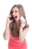 Frau, die eine Kreditkarte bei der Unterhaltung am Telefon zeigt Lizenzfreie Stockfotografie