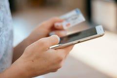 Frau, die eine Kreditkarte hält und Handy für das on-line-Einkaufen verwendet Stockbild