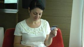 Frau, die eine Kreditkarte hält und vom Internet kauft stock footage