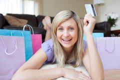 Frau, die eine Kreditkarte nach dem Einkauf anhält Lizenzfreie Stockfotografie