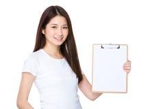Frau, die eine Leerseite des Klemmbrettes zeigt Lizenzfreies Stockbild