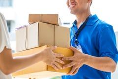 Frau, die eine Lieferung von Pappschachteln vom Lieferboteen annimmt Stockbild