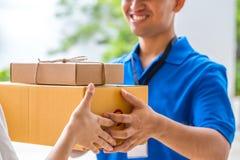 Frau, die eine Lieferung von Pappschachteln vom Lieferboteen annimmt Stockfoto