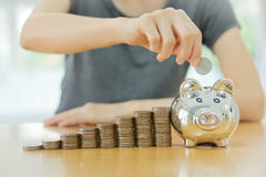 Frau, die eine Münze in einen Geld-Kastenabschluß u setzt Lizenzfreie Stockbilder