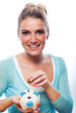 Frau, die eine Münze in ihr Sparschwein setzt Lizenzfreies Stockfoto