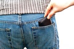 Frau, die eine Mappe von der rückseitigen Tasche des Mannes stiehlt Lizenzfreie Stockfotos