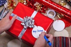 Frau, die eine Marke für ihre Weihnachtsgeschenke schreibt. Lizenzfreie Stockfotografie