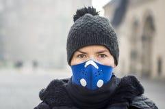 Frau, die eine Maske, vor Smog schützend verwendet stockfotos