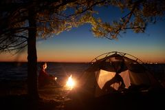 Frau, die eine Nachtzeit kampiert nahe touristischem Zelt, Lagerfeuer auf Seeufer unter sternenklarem Himmel hat lizenzfreies stockfoto