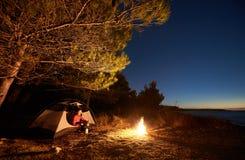 Frau, die eine Nachtzeit kampiert nahe touristischem Zelt, Lagerfeuer auf Seeufer unter sternenklarem Himmel hat lizenzfreie stockfotos
