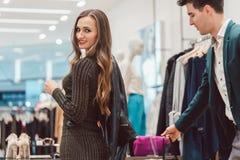 Frau, die eine neue Lederjacke in der Hüftenmodeboutique versucht Lizenzfreie Stockfotos