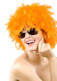 Frau, die eine orange Federperücke und -sonnenbrillen trägt Lizenzfreies Stockfoto