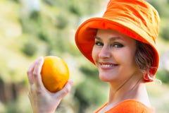 Frau, die eine Orange hält Lizenzfreie Stockfotografie