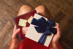 Frau, die eine Pappgeschenkbox mit blauem Band öffnet Lizenzfreie Stockfotos