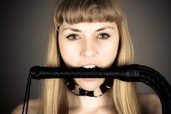 Frau, die eine Peitsche in seinem Mund hält Stockfotos