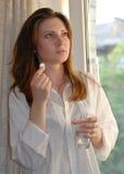 Frau, die eine Pille und ein Glas Wasser anhält Stockfotos