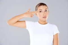 Frau, die eine Pistolengeste macht lizenzfreies stockbild