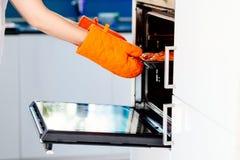 Frau, die eine Pizza vom elektrischen Ofen zieht Stockfotografie