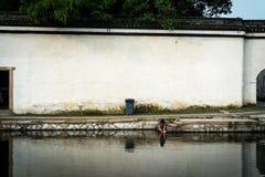 Frau, die eine Platte in einem Kanal säubert Stockbilder