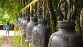 Frau, die eine Reihe von Tempelglocken in Thailand schellt Stockfotografie