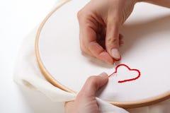 Frau, die eine rotes Herz-geformte Dekoration näht Lizenzfreies Stockbild