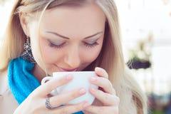 Frau, die eine Schale des heißen Getränks riecht Lizenzfreies Stockfoto